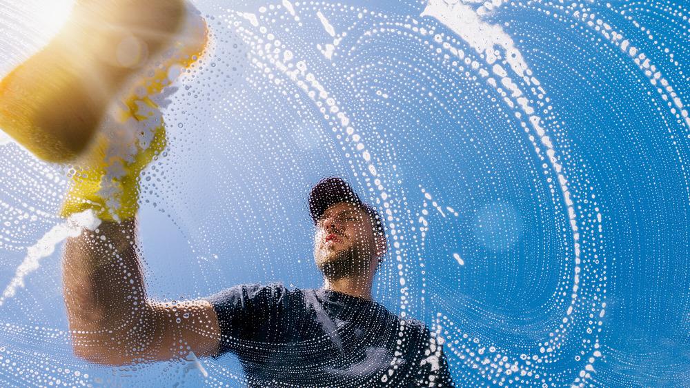 A man washing windows with a sponge