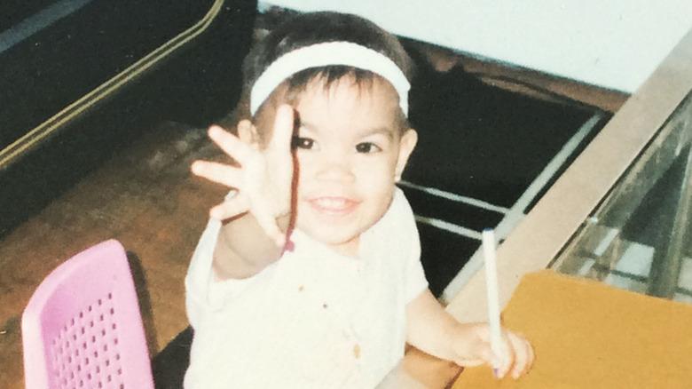 Alexandria Ocasio-Cortez as a little kid reaching out