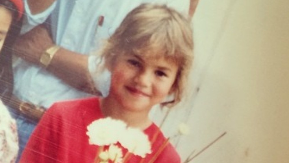 Chrissy Teigen as a young girl holding flowers