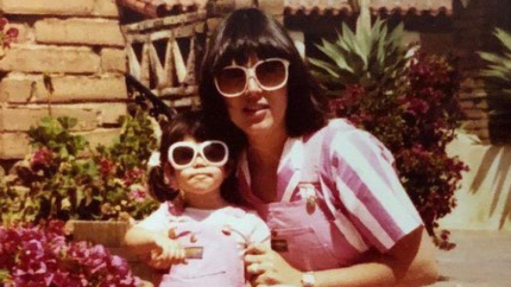 Kourtney Kardashian as a girl with her mother, wearing sunglasses