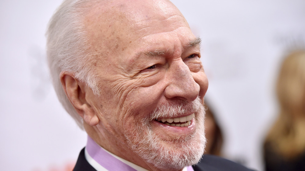 Christopher Plummer smiling with white backdrop