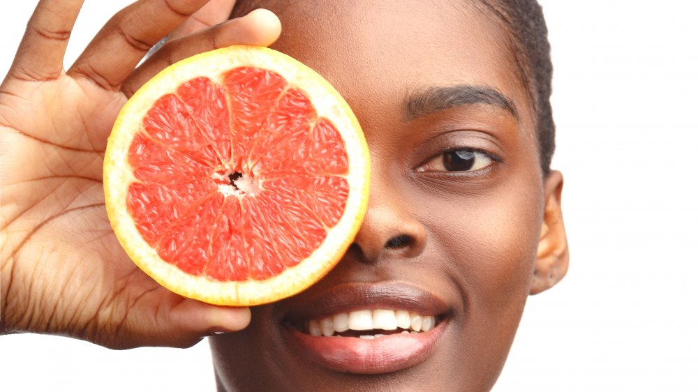 Woman holding a grapefruit in front of her face