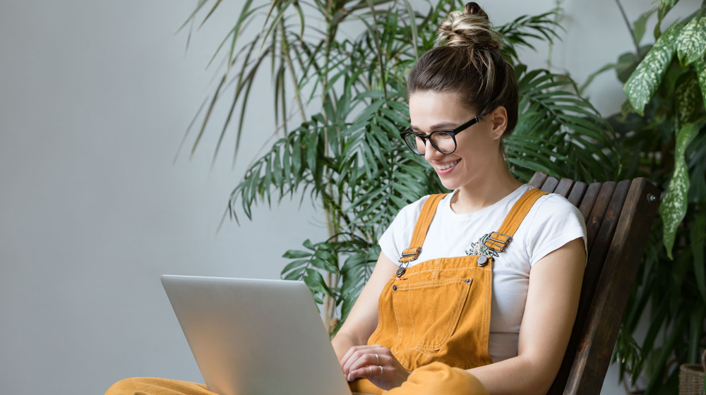 Woman on laptop with houseplants
