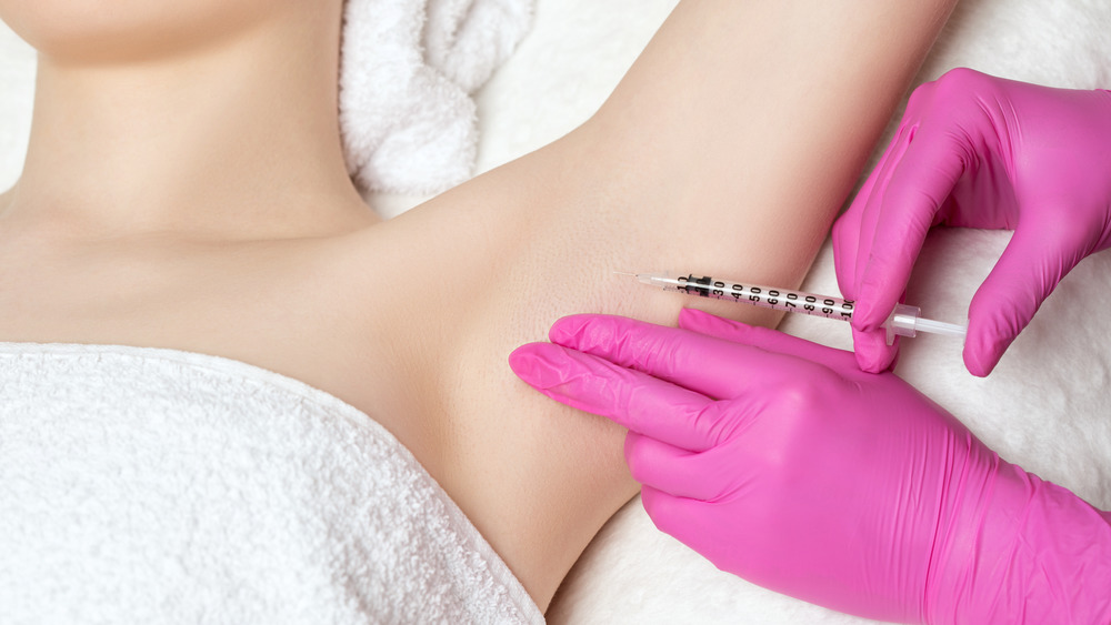 A woman receiving a Botox injection in her armpit
