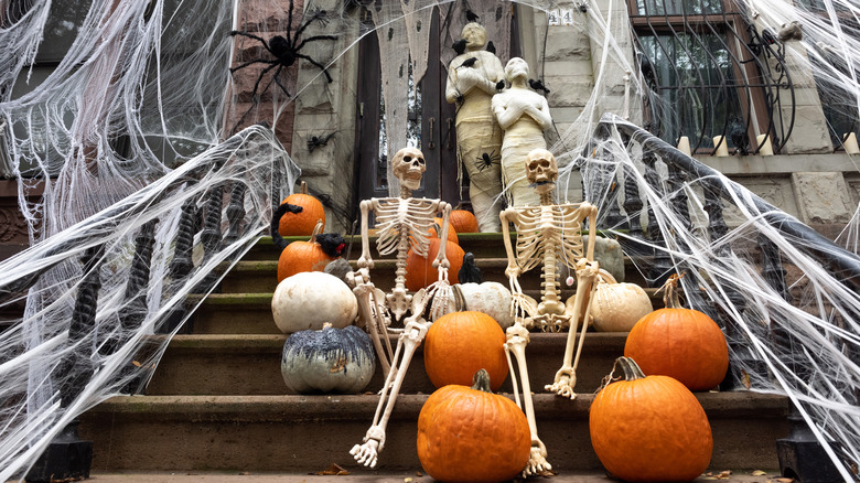 home in new york decorated for halloween with spiders, skeletons, mummies, pumpkins, and spiderwebs