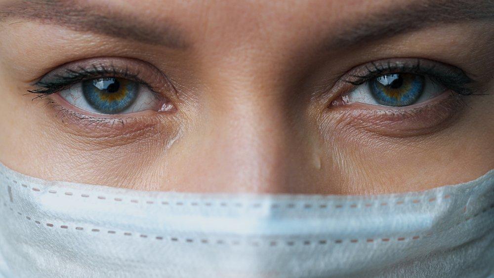 Woman wearing mask, eyes tearing