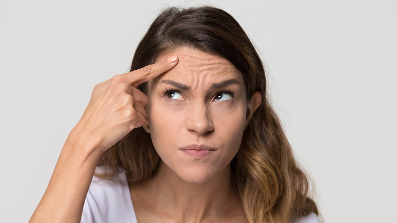 Woman looking annoyed and stress pointing at a pimple on her forehead