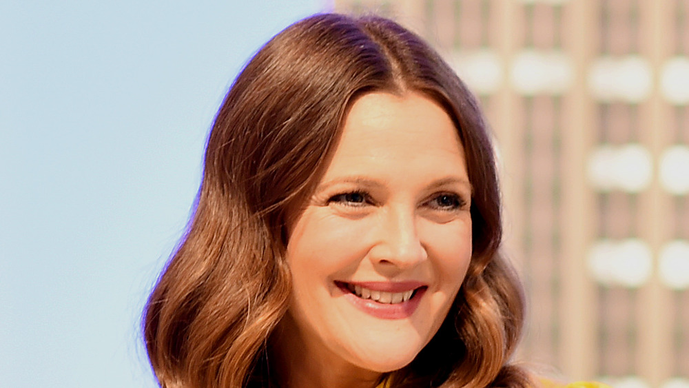Drew Barrymore smiling hair parted down the middle looking off to the side