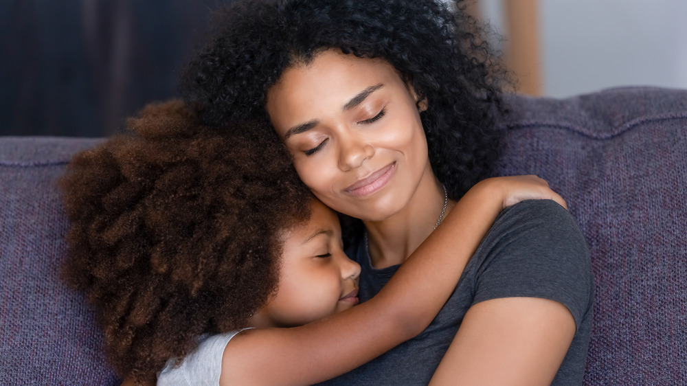 Woman and little girl hugging with their eyes closed