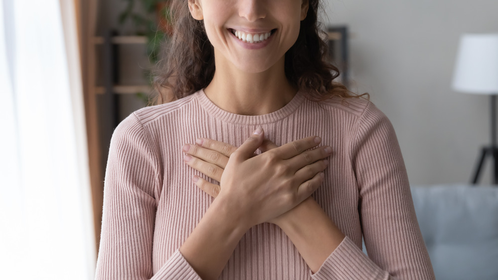 Smiling woman with her hands on her chest
