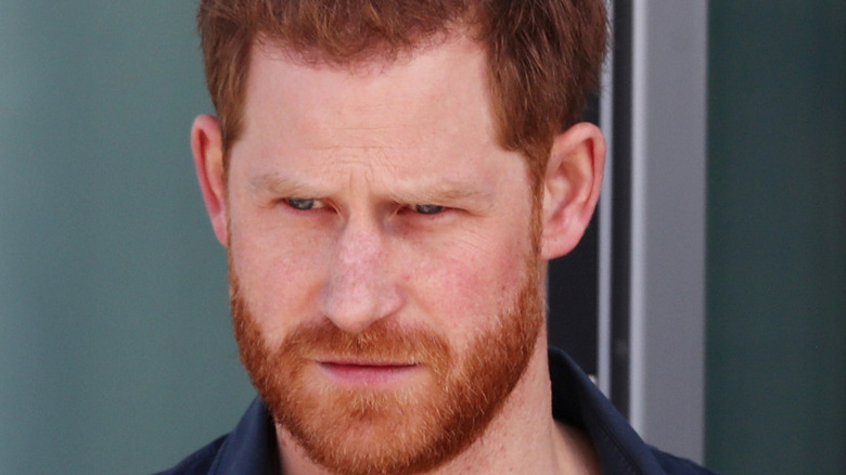 Prince Harry looking serious with facial hair