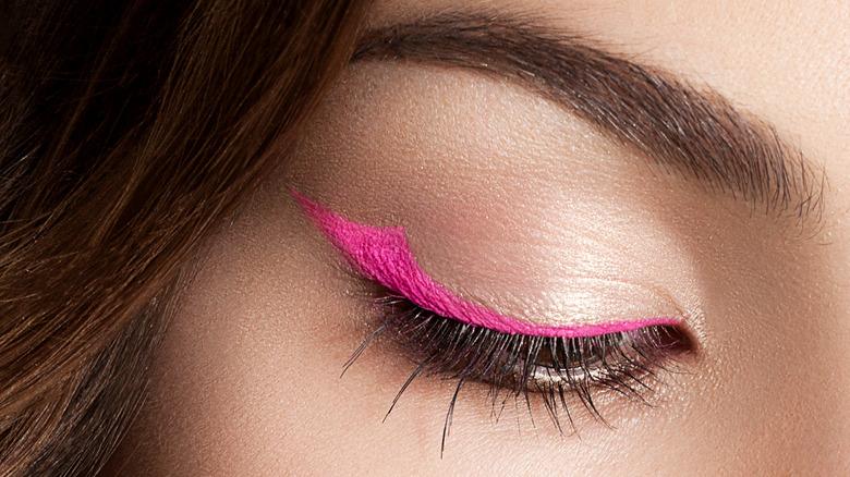 close up of woman wearing pink eyeliner