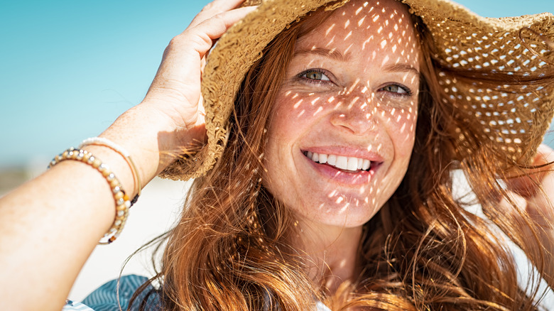smiling woman with freckles wearing sunhat