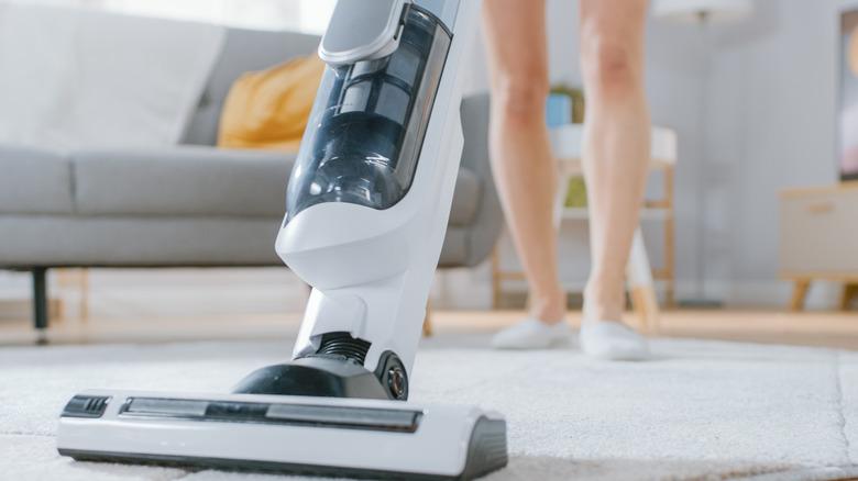 Woman vacuuming a rug.
