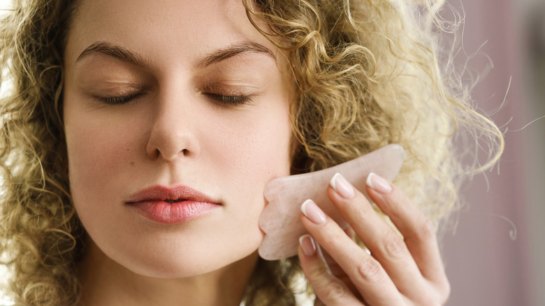 Woman using a gua sha for facial massage