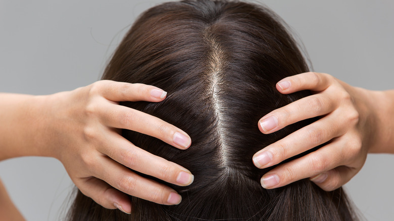 A woman parting her hair with her hands