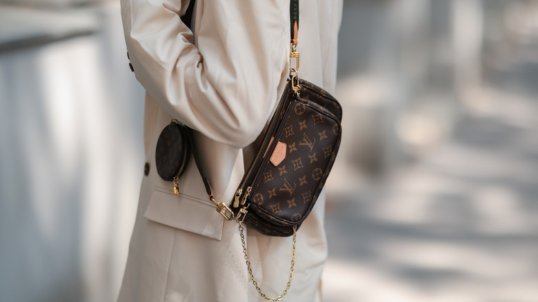 Woman carrying a small Louis Vuitton bag