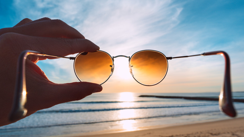 Sunglasses being held up over the sunlight ocean