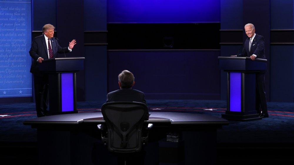 Debate stage wide shot with debaters, moderator