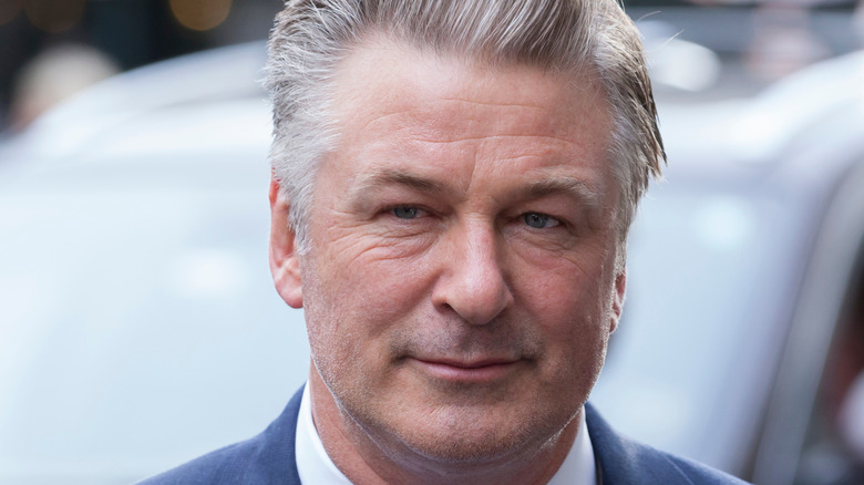 Alec Baldwin gives a slight smile with his gray hair slicked back.