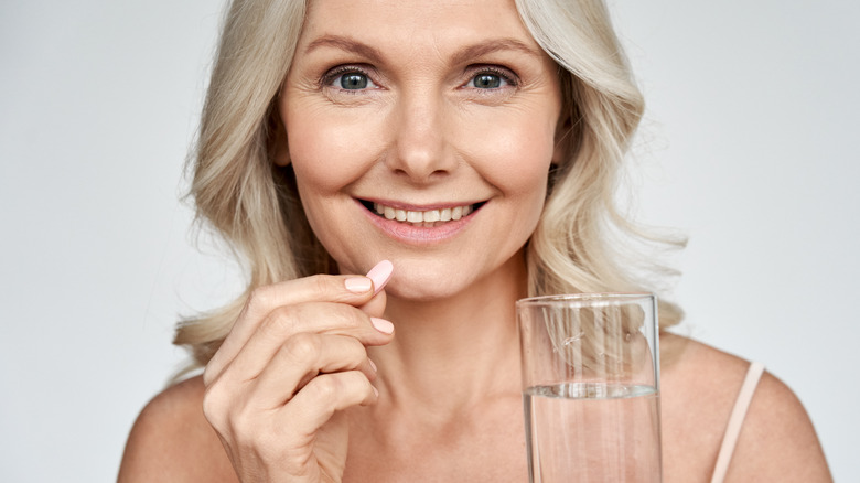 Smiling woman taking supplement with galss of water