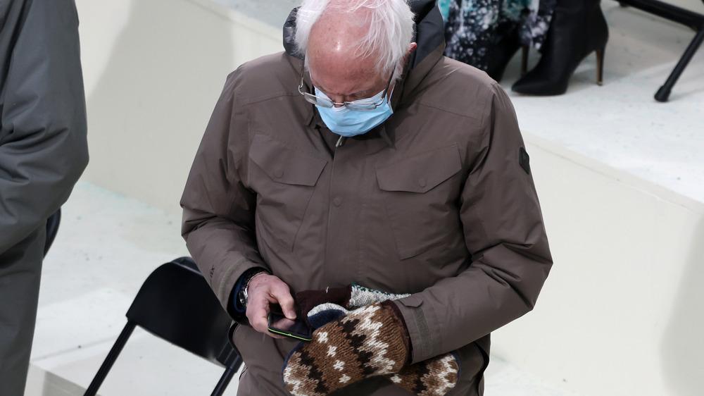Bernie Sanders checking phone wearing mittens