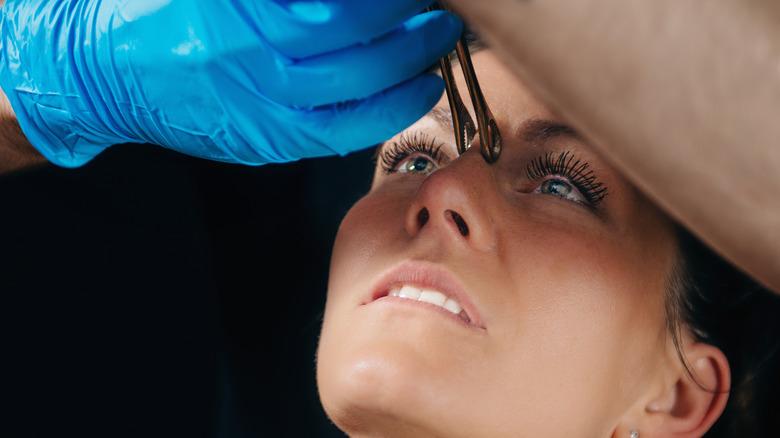 Woman getting her bridge piercing