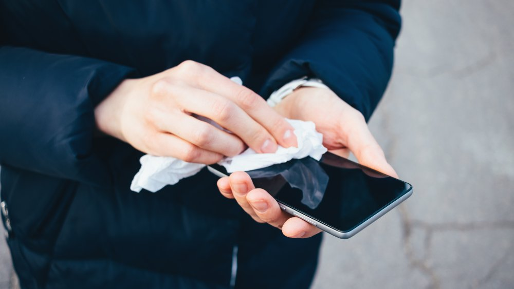 Woman wiping a cell phone