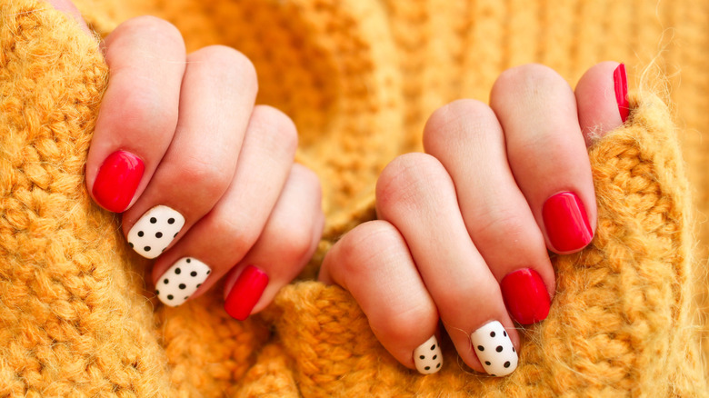 Woman with colorful manicured nails against a chunky knit yellow sweater.