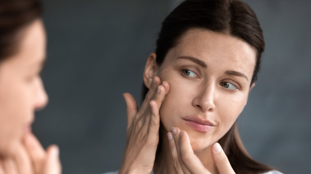 Woman looking at blemishes on her face