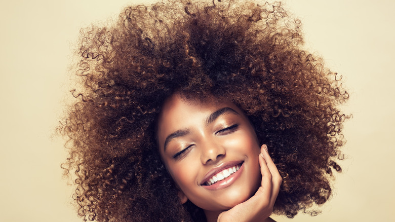 A woman with curly hair, smiling