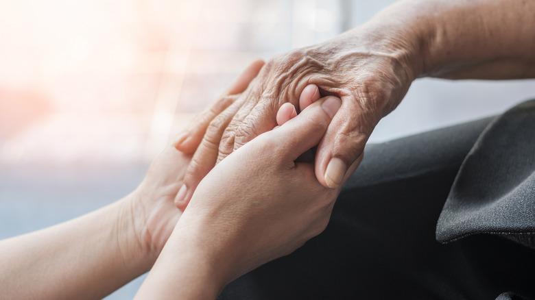Younger hands holding wrinkled hands