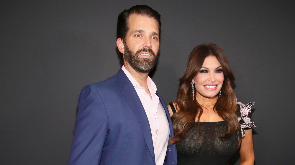 Donald Trump Jr. in blue suit and Kimberly Guilfoyle in black sheer dress