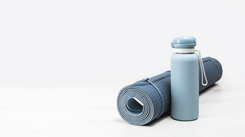 Rolled yoga mat next to a water bottle