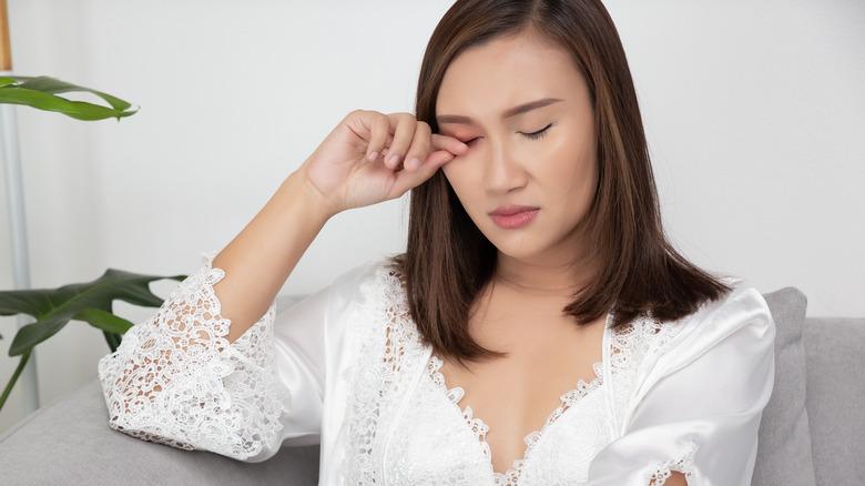 woman rubbing eyelid