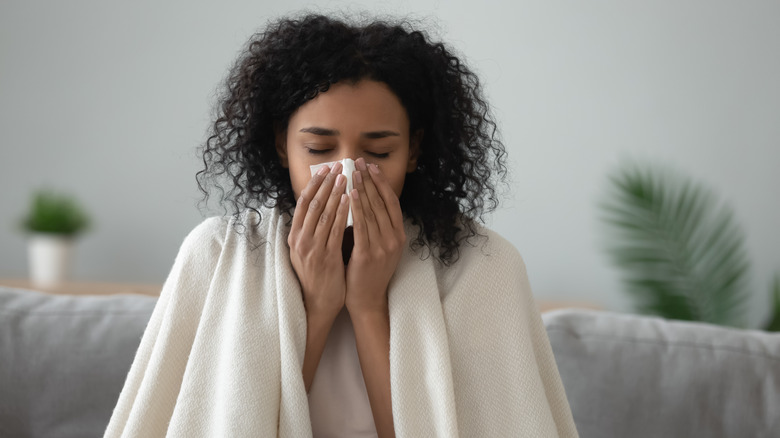 Woman sick blows her nose into a tissue
