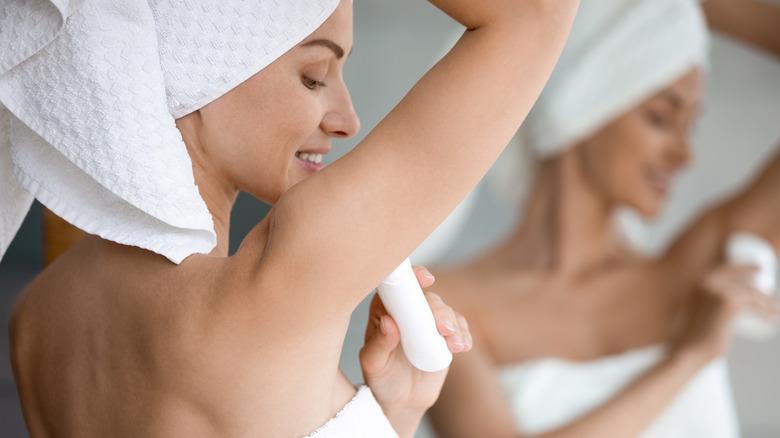 A woman puts on deodorant