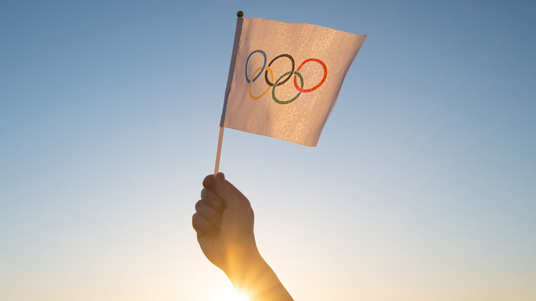 Person holding flag with Olympic rings
