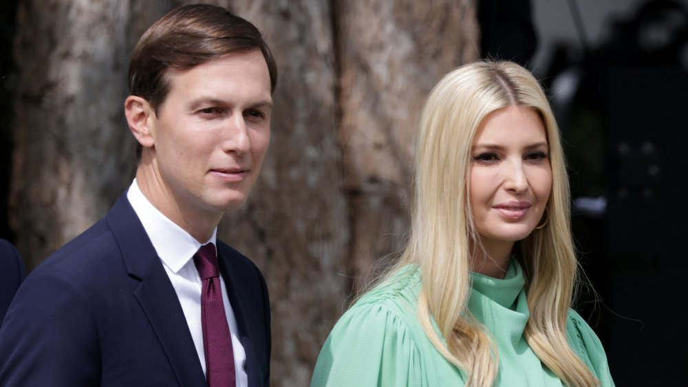 Jared Kushner and Ivanka Trump, walking outside with small smiles and looking off to the side