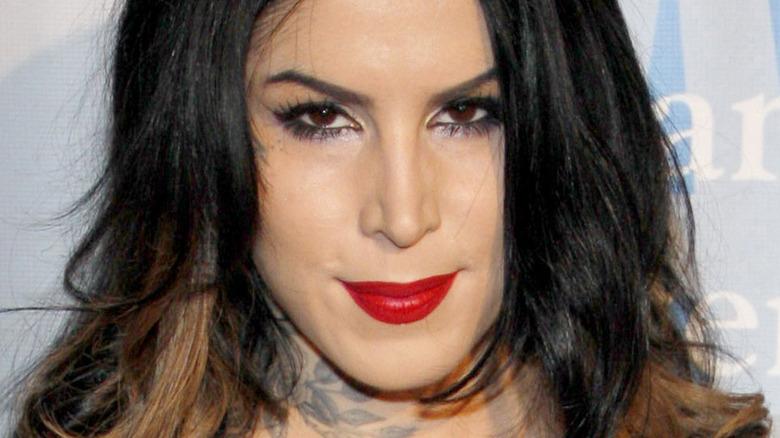 Kat Von D head tilted down grinning in red lip