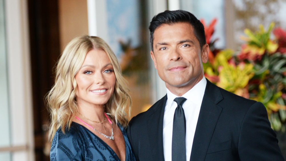 Kelly Ripa and Mark Consuelos in front of flowers