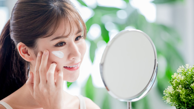 A woman looking at herself in the mirror while applying sunscreen on her face