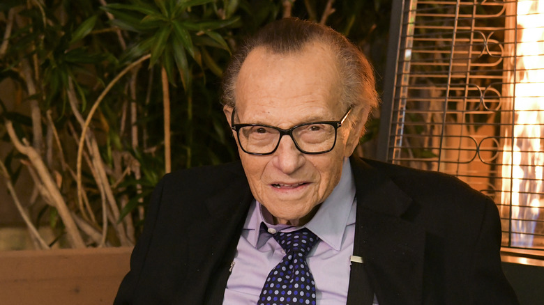 Larry King in front of plants