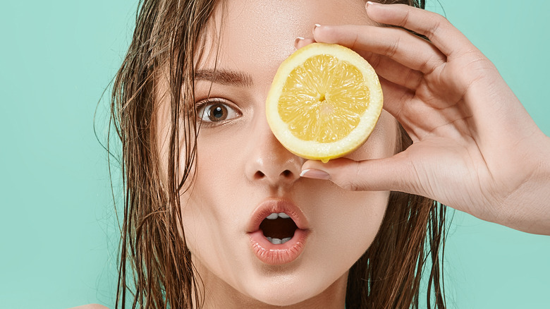 Woman with damp hair holding a cut lemon in front her her eye