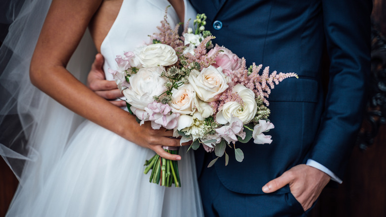 Woman holding a bouquet of flowers next to man