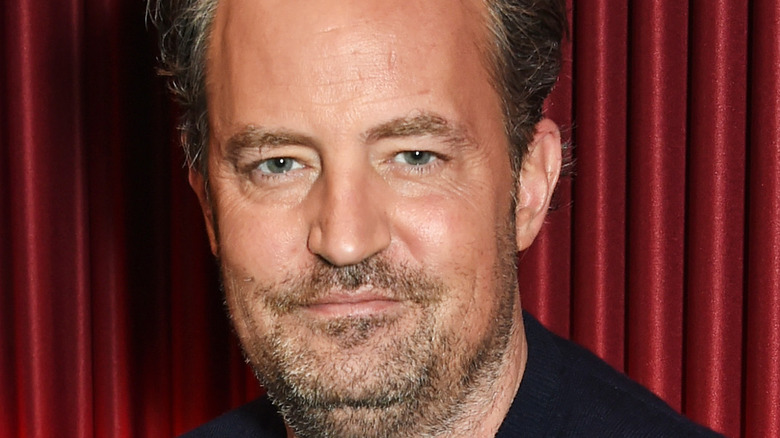 Matthew Perry grinning with facial hair