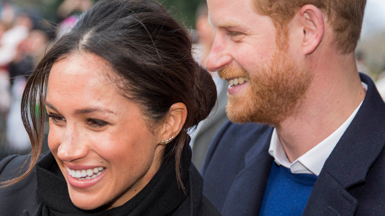 Meghan and Harry smile and greet fans