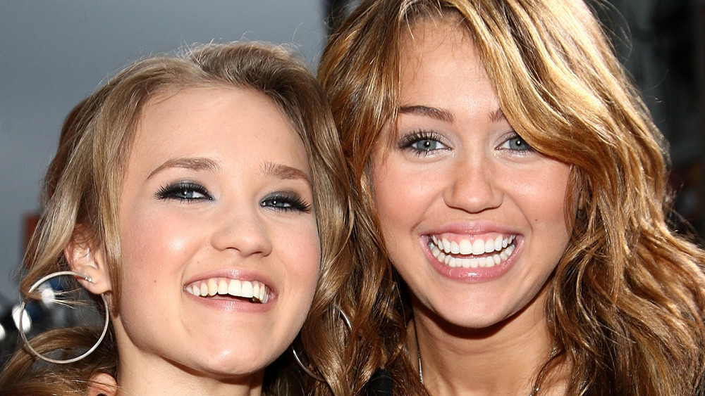 Emily Osment and Miley Cyrus pose
