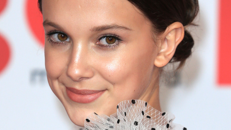 Millie Bobby Brown smiling and looking to the side