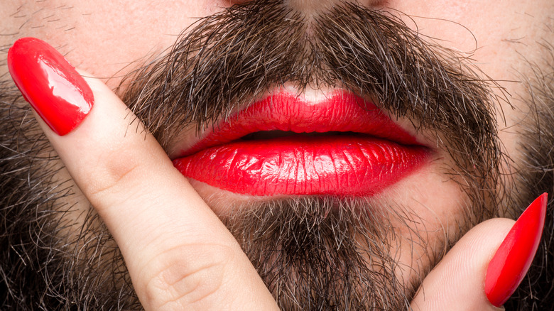 Bearded face with red lipstick, red nail polish